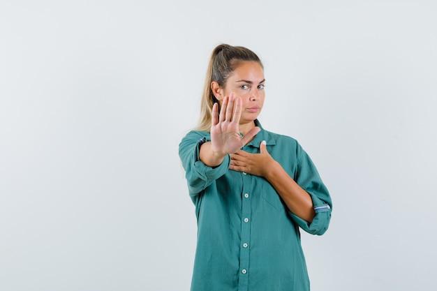 Junge frau im blauen hemd, das ablehnungsgeste zeigt und ernst schaut
