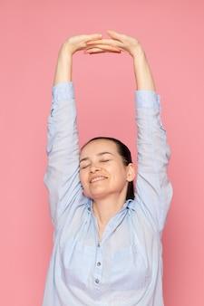 Junge frau im blauen hemd, das auf der rosa wand aufwirft