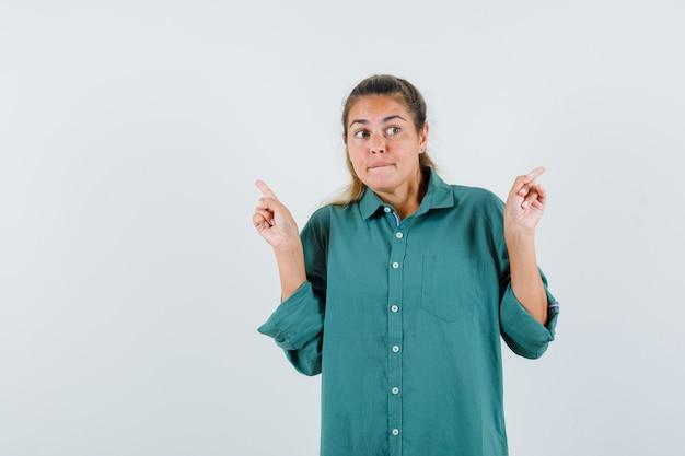 Junge frau im blauen hemd, das auf die rückseite zeigt und verwirrt schaut
