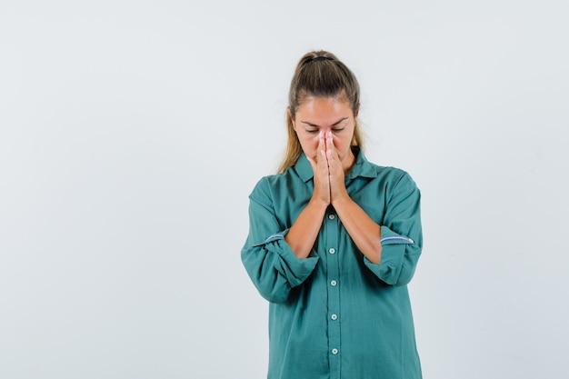 Junge frau im blauen hemd, das für etwas betet und hoffnungsvoll aussieht