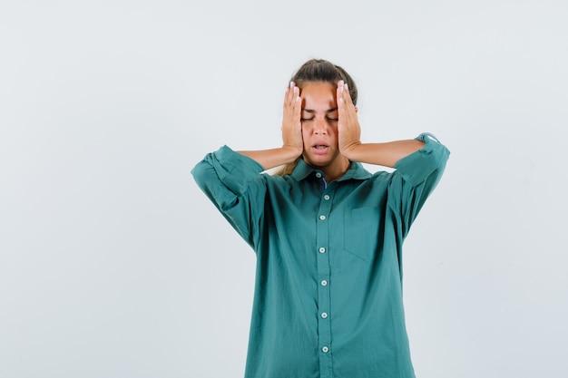 Junge frau im blauen hemd, das hände auf ihren wangen hält und gelangweilt aussieht