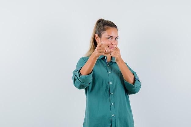 Junge frau im blauen hemd, das nach vorne zeigt und erfreut schaut
