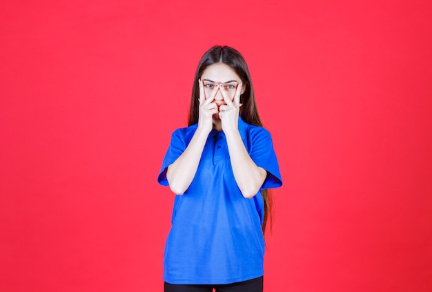 Junge frau im blauen hemd, die auf roter wand steht und friedenszeichen zeigt