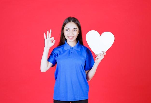 Junge frau im blauen hemd, die eine weiße herzfigur hält und positives handzeichen zeigt
