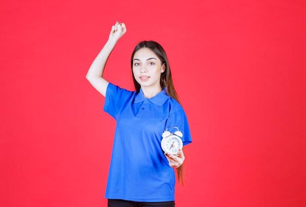 Junge frau im blauen hemd, die einen wecker hält und positives handzeichen zeigt