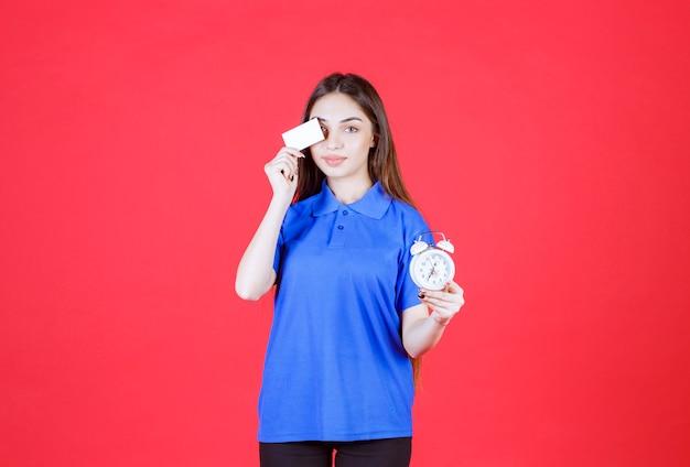 Junge frau im blauen hemd hält einen wecker und präsentiert ihre visitenkarte