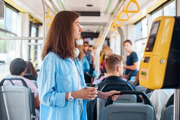 Junge frau im blauen hemd reitet in der modernen straßenbahn oder im bus mit tasse kaffee zum mitnehmen.