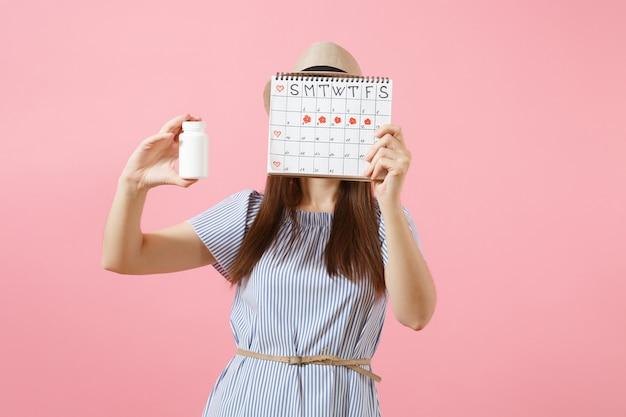 Junge frau im blauen kleid, die weiße flasche mit pillen hält, deckt den kalender der zeiträume ab und überprüft die menstruationstage einzeln auf dem hintergrund. gynäkologisches konzept des medizinischen gesundheitswesens. platz kopieren.
