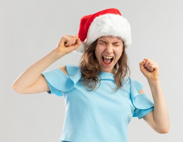 Junge frau im blauen oberteil und im weihnachtsmannhut, die fäuste ballen, die mit aggressivem ausdruck verrückt verrückt schreien