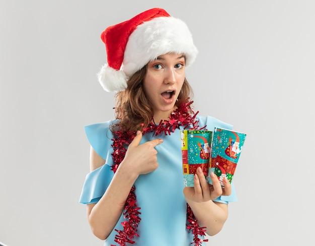Junge frau im blauen oberteil und im weihnachtsmannhut mit lametta um ihren hals, der bunte pappbecher hält, die überrascht auf sich selbst zeigen