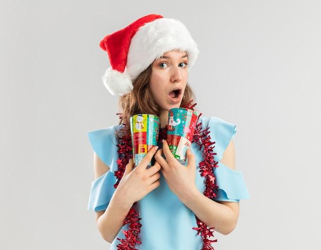 Junge frau im blauen oberteil und im weihnachtsmannhut mit lametta um ihren hals, der bunte pappbecher hält, die überrascht schauen