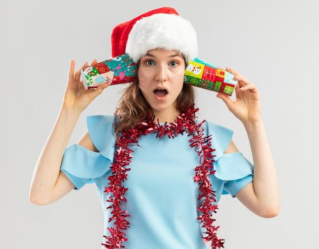 Junge frau im blauen oberteil und im weihnachtsmannhut mit lametta um ihren hals, der bunte pappbecher über ihren ohren hält und überrascht aussieht