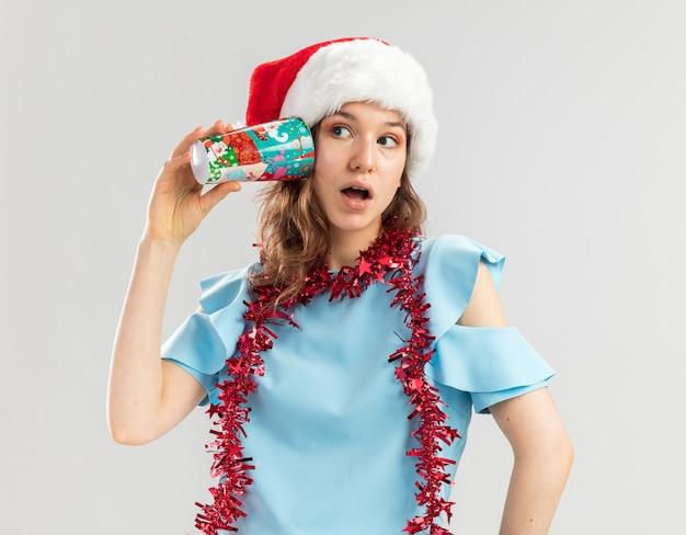 Junge frau im blauen oberteil und im weihnachtsmannhut mit lametta um ihren hals, der bunten pappbecher über ihrem ohr fasziniert hält