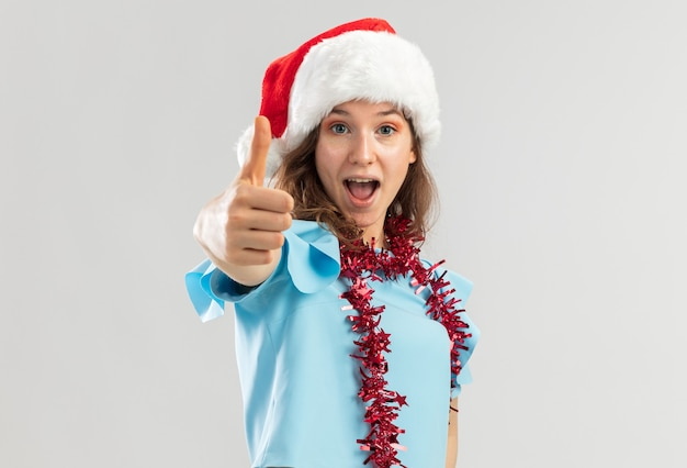 Junge frau im blauen oberteil und im weihnachtsmannhut mit lametta um ihren hals, der glücklich und aufgeregt zeigt daumen zeigt