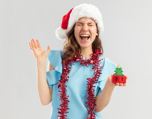 Junge frau im blauen oberteil und im weihnachtsmannhut mit lametta um ihren hals, der spielzeugwürfel mit glücklichem ney jahresdatum hält, das verrückt glücklich schreit