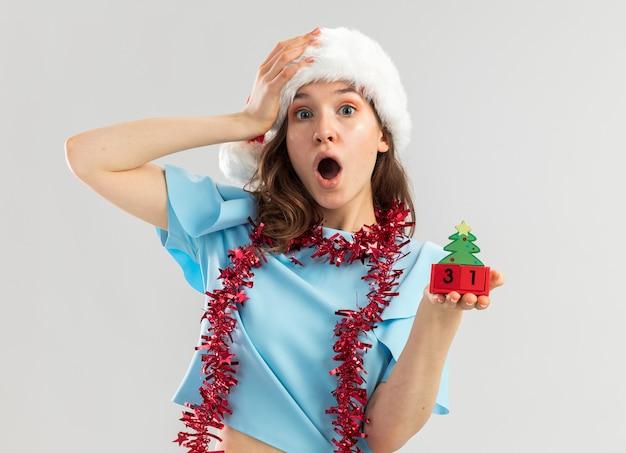 Junge frau im blauen oberteil und im weihnachtsmannhut mit lametta um ihren hals, der spielzeugwürfel mit neujahrsdatum hält, das mit hand auf ihrem kopf erstaunt schaut
