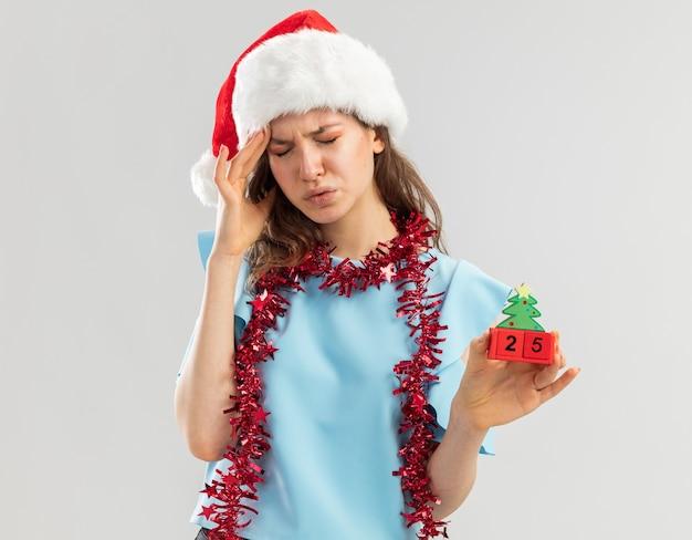 Junge frau im blauen oberteil und im weihnachtsmannhut mit lametta um ihren hals, der spielzeugwürfel mit weihnachtsdatum hält, das unwillig aussieht und starke kopfschmerzen hat, die ihren kopf berühren