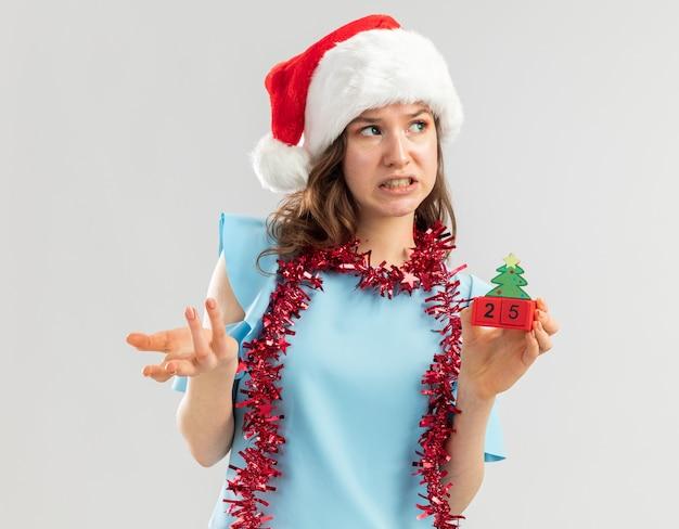 Junge frau im blauen oberteil und im weihnachtsmannhut mit lametta um ihren hals, der spielzeugwürfel mit weihnachtsdatum hält, das verwirrt und unzufrieden mit dem arm heraus schaut