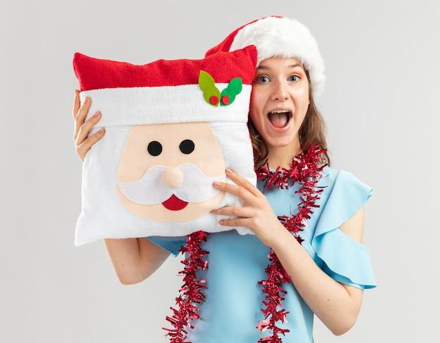 Junge frau im blauen oberteil und im weihnachtsmannhut mit lametta um ihren hals, der weihnachtskissen hält, das fröhlich und positiv lächelnd fröhlich schaut