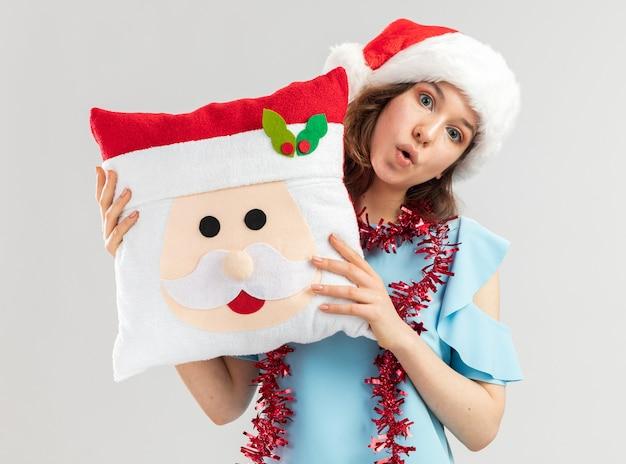 Junge frau im blauen oberteil und im weihnachtsmannhut mit lametta um ihren hals, der weihnachtskissen hält, das überrascht schaut
