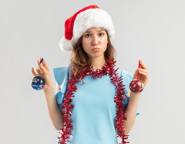 Junge frau im blauen oberteil und im weihnachtsmannhut mit lametta um ihren hals, der weihnachtskugeln hält, die verwirrt und unzufrieden aussehen