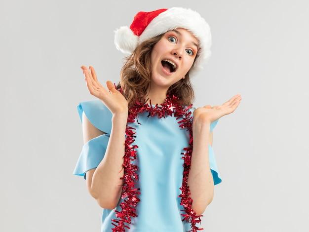 Junge frau im blauen oberteil und im weihnachtsmannhut mit lametta um ihren hals verrückt glücklich und aufgeregt schreiend