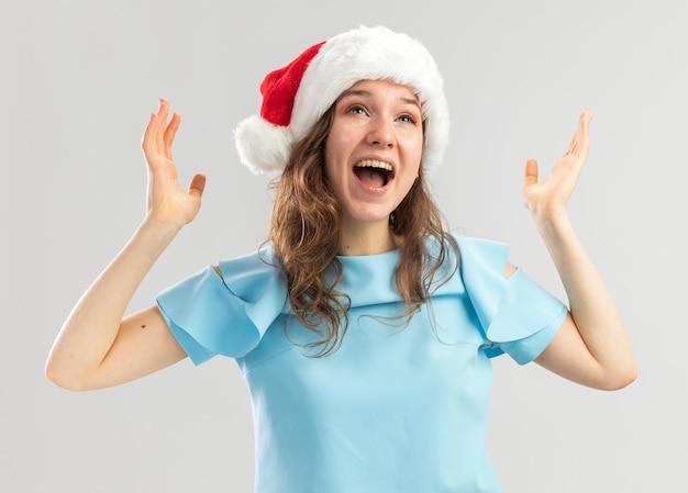 Junge frau im blauen oberteil und in der weihnachtsmannmütze, die mit den armen schreien, die verrückt glücklich und aufgeregt erhoben