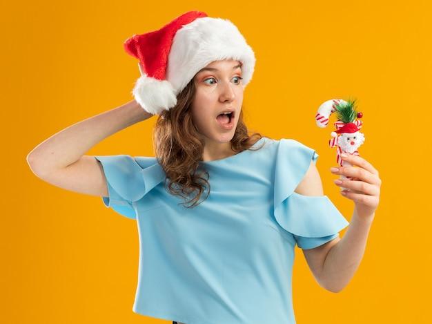 Junge frau im blauen oberteil und in der weihnachtsmannmütze, die weihnachtszuckerstange hält, die es mit der hand auf ihrem kopf erstaunt betrachtet