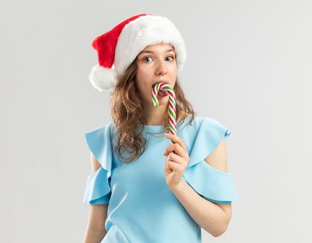 Junge frau im blauen oberteil und in der weihnachtsmannmütze, die zuckerstange hält, glücklich und freudig, es zu schmecken
