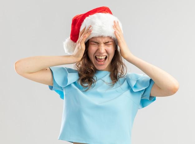 Junge frau im blauen oberteil und in der weihnachtsmütze, die mit genervtem ausdruck mit den händen auf ihrem kopf schreien