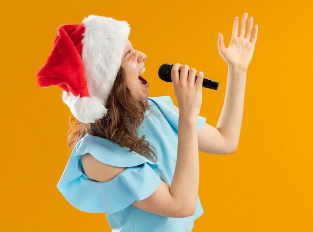 Junge frau im blauen oberteil und in der weihnachtsmütze, die zum mikrofon schreit, erregte verrückte emotionale mit erhobenem arm