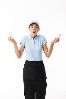 Junge frau im blauen polo-t-shirt und in der kappe, die in den händen einwegbecher halten, während erstaunt