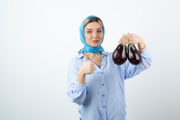 Junge frau im blauen schal, der daumen oben zeigt und ungekochte auberginen hält