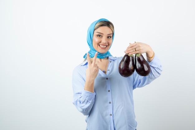Junge frau im blauen schal, der siegeszeichen zeigt und ungekochte auberginen hält