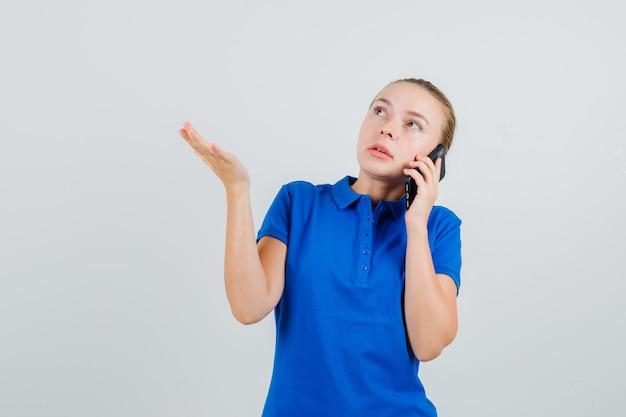 Junge frau im blauen t-shirt, das auf handy spricht und nachdenklich schaut