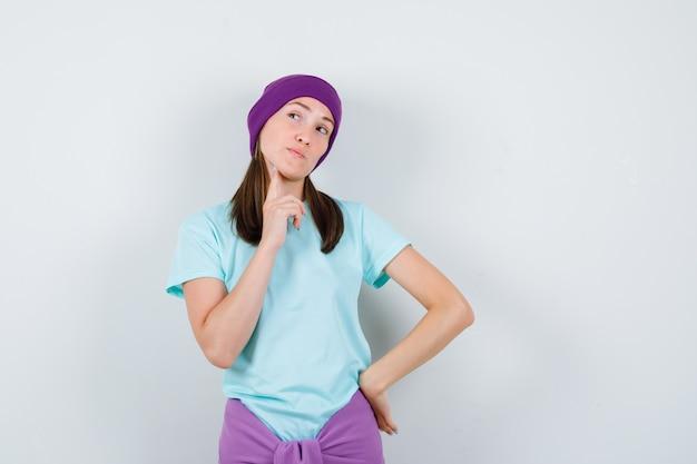 Junge frau im blauen t-shirt, lila mütze mit zeigefinger auf der wange, legt eine hand auf die hüfte, denkt an etwas und sieht nachdenklich aus, vorderansicht.