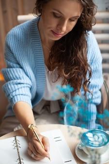 Junge frau im blauen warmen pullover, der nahe dem großen fenster des coffeeshops sitzt und eine weihnachtseinkaufsliste mit tasse des blauen latte schreibt. weihnachtsferien planen. organisations- und planungskonzept.