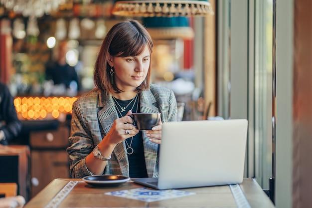 Junge frau im blazer mit laptop im café am fenster. berufe ist bloggerin, freiberuflerin und autorin. freiberufler, der im café arbeitet. online-lernen.