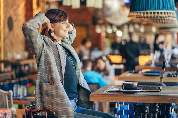 Junge frau im blazer träumt von etwas mit tragbarem netbook im café am fenster mit kaffee. herbstmorgen.