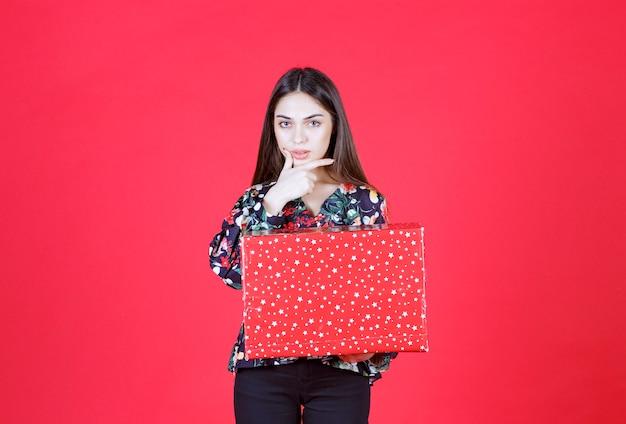 Junge frau im blumenhemd, die eine rote geschenkbox mit weißen punkten darauf hält und verwirrt und nachdenklich aussieht