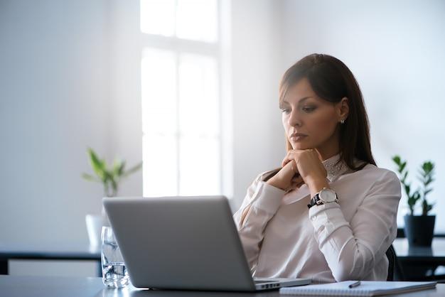 Junge frau im büro, das mit einem laptop arbeitet