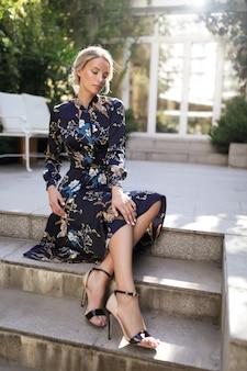 Junge frau im bunten kleid sitzt auf der stufe, dünn, mode, frisur, glamourös, schuhe, im freien, perfekter körper, blondine, schönheit, make-up, sonnenschein