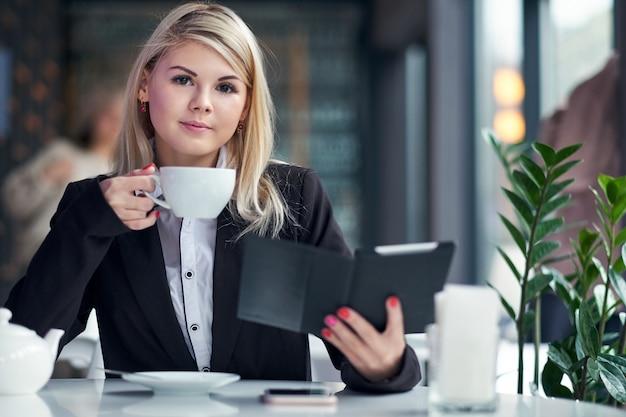 Junge frau im café, das ein ebook liest und kaffee trinkt