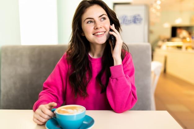 Junge frau im café, die kaffee trinkt und am telefon spricht
