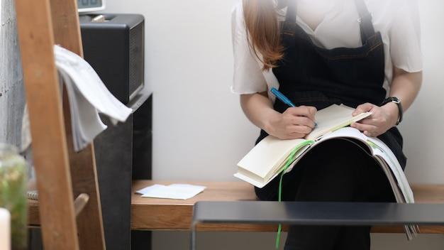Junge frau im café schreibt notizen auf notebook