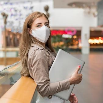 Junge frau im einkaufszentrum mit laptop, die maske trägt