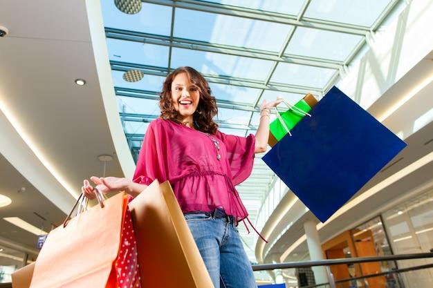 Junge frau im einkaufszentrum mit taschen einkaufen
