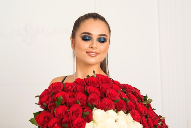 Junge frau im eleganten kleid, das bouguet von hundert roten rosen hält