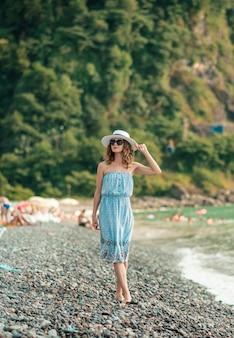 Junge frau im farbbikini, der den sommertanz genießt. frau, die sich am meer sonnen. sommerferien, ferien, entspannen. mädchen sonnenbaden am strand im badeanzug