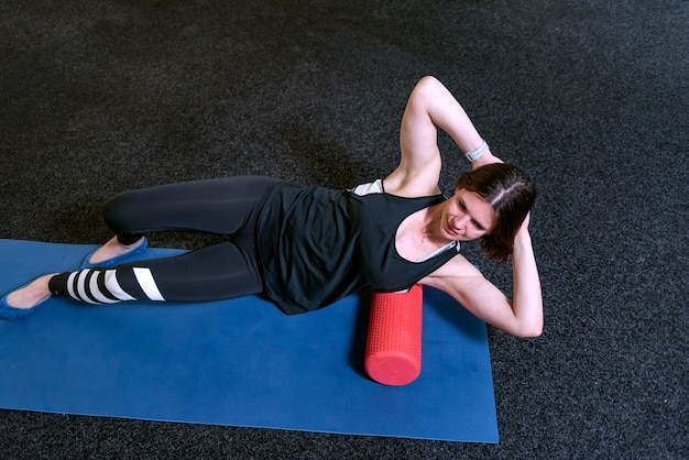 Junge frau im fitnessstudio massiert ihre muskeln mit mfr-rollen. myofasziale freisetzung mit schaumstoffrolle. mfr.
